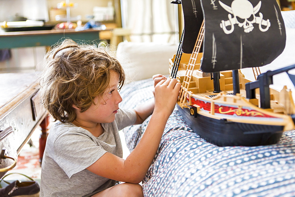 6 year old boy playing with a toy pirate ship at home