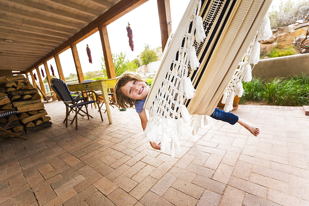 A six year old boy swinging on hammock under patio