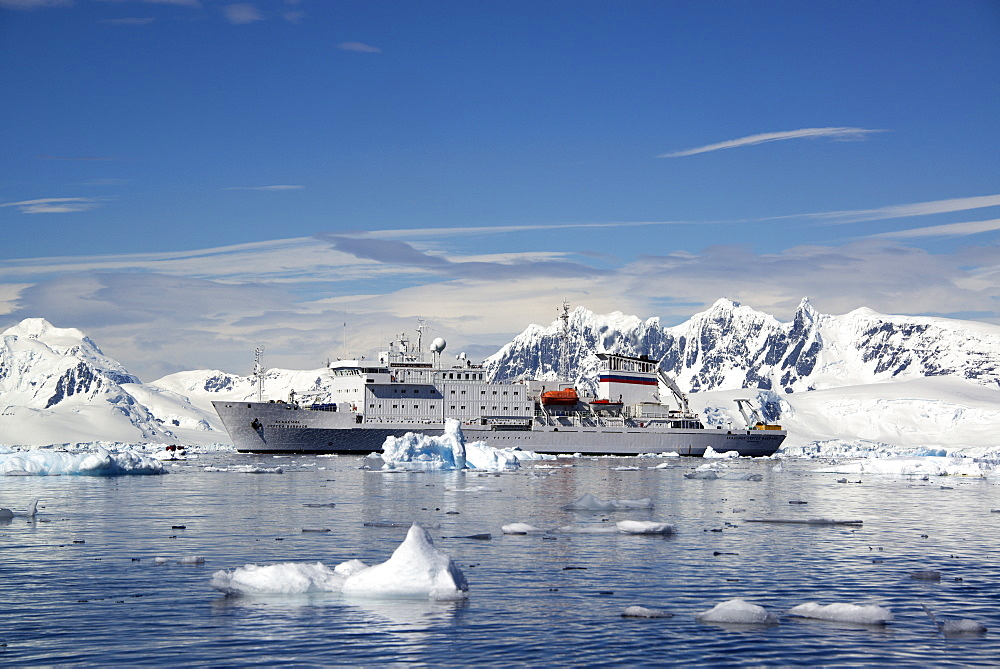 An Antarctic cruise ship with inflatable zodiacs on the calm waters among ice floes and mountainous landscape, Antarctic peninsula, Antarctica