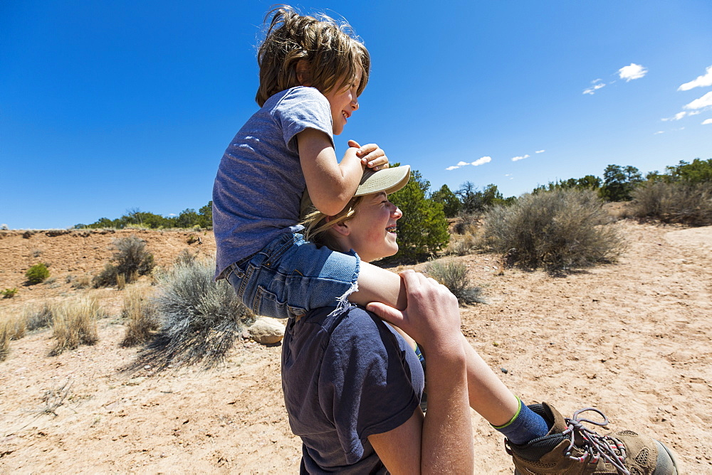 14 year old girl giving younger brother a piggyback ride, Galisteo Basin, New Mexico, United States of America