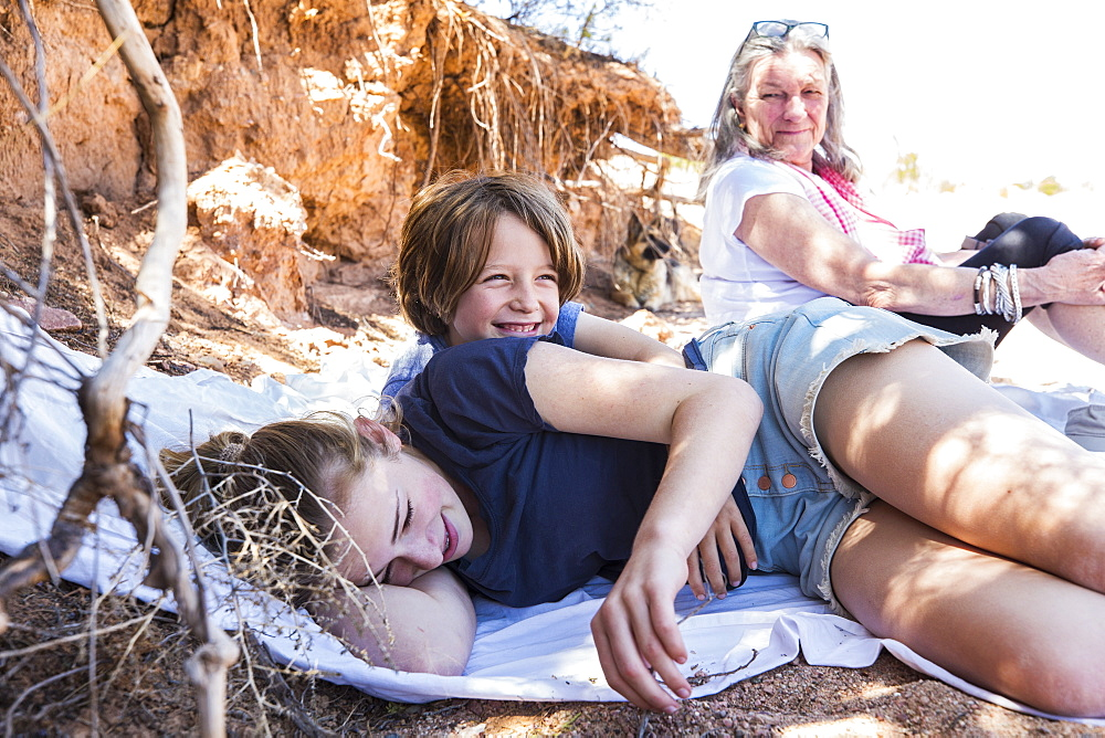 Two children and grandmother in background, resting after a hike