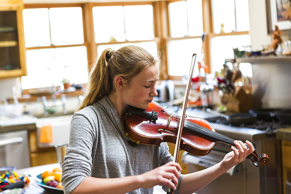 13 year old girl playing violin at home