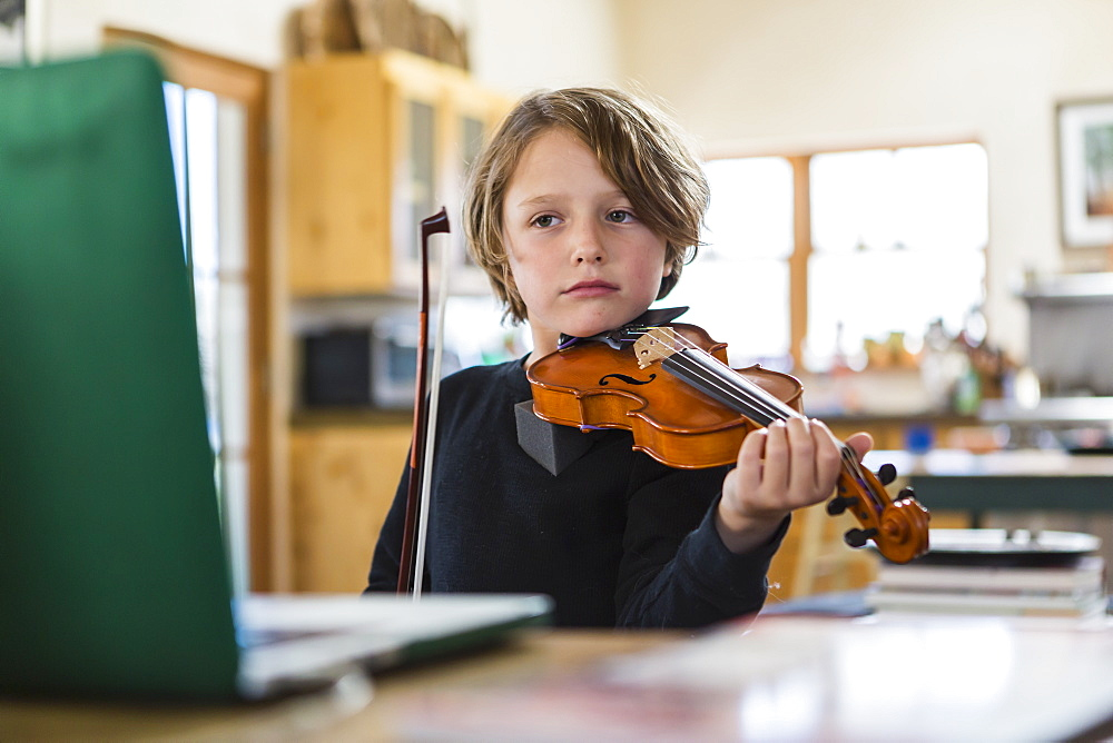 Six year old boy playing violin, having a remote video lesson in lockdown at home