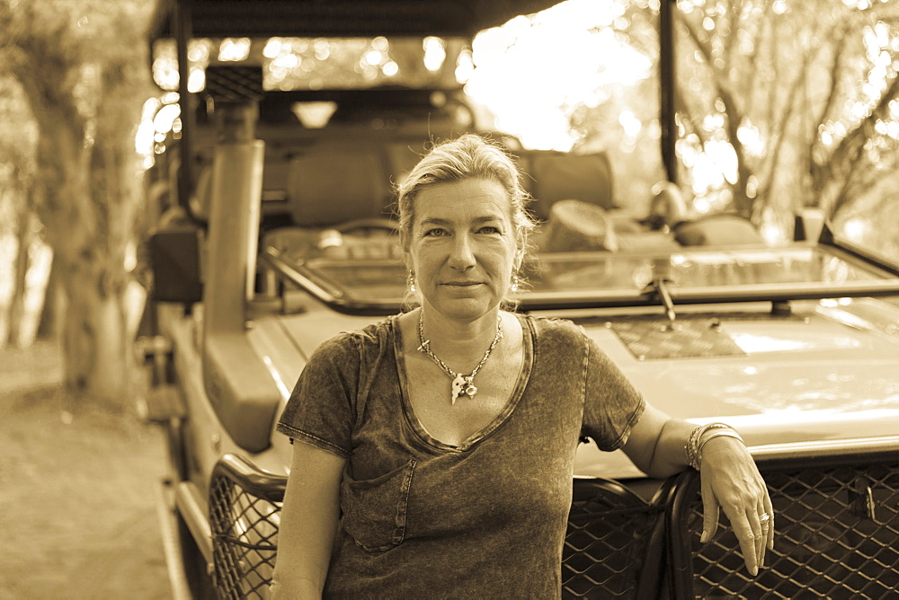 Portrait of woman leaning on a safari vehicle, Moremi Game Reserve, Botswana