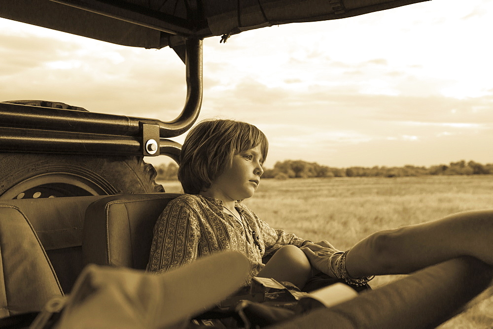 Five year old boy seated in a safari vehicle, monochrome, Moremi Game Reserve, Botswana