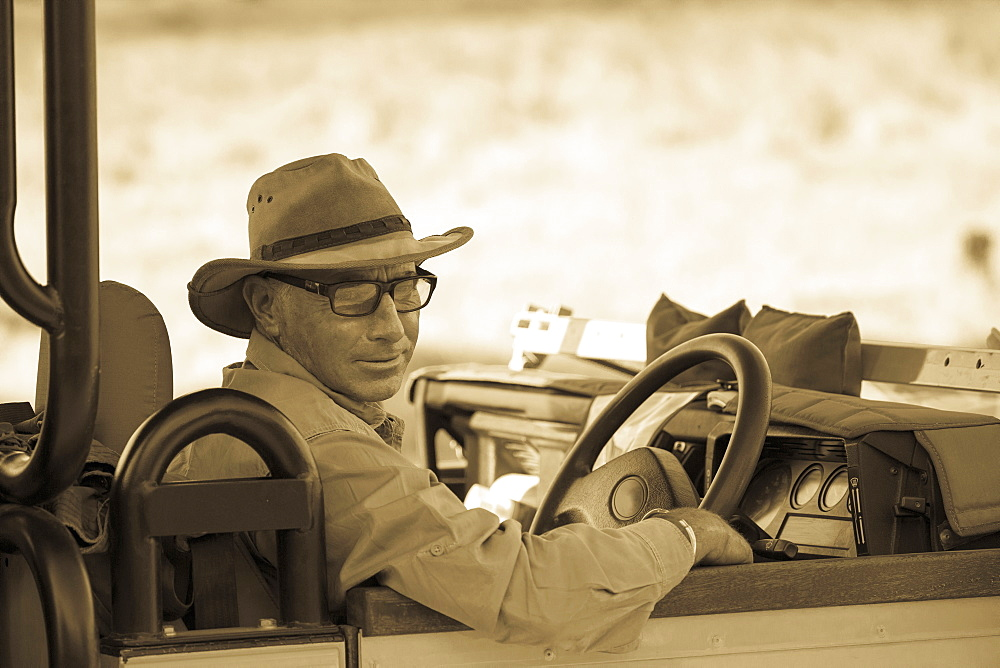 A mature man in hat and glasses in the driving seat of a jeep, sepia tone, Moremi Game Reserve, Botswana