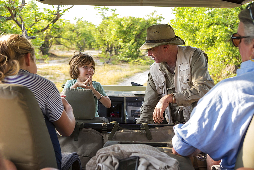 A family of visitors in a safari vehicle with a guide, Moremi Game Reserve, Botswana