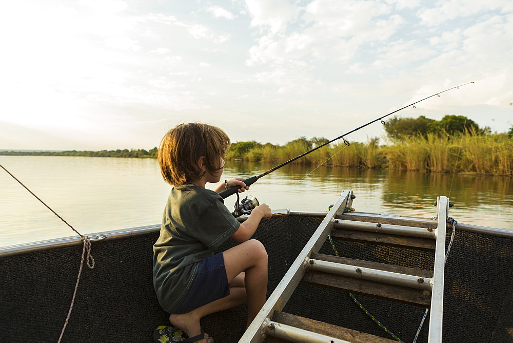 A five year old boy fishing from a boat on the Zambezi River, Botswana, Zambezi River, Botswana