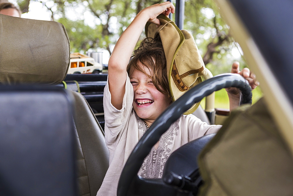 Portrait of smiling Six year old boy with a large hat in the driving seat of a safari vehicle