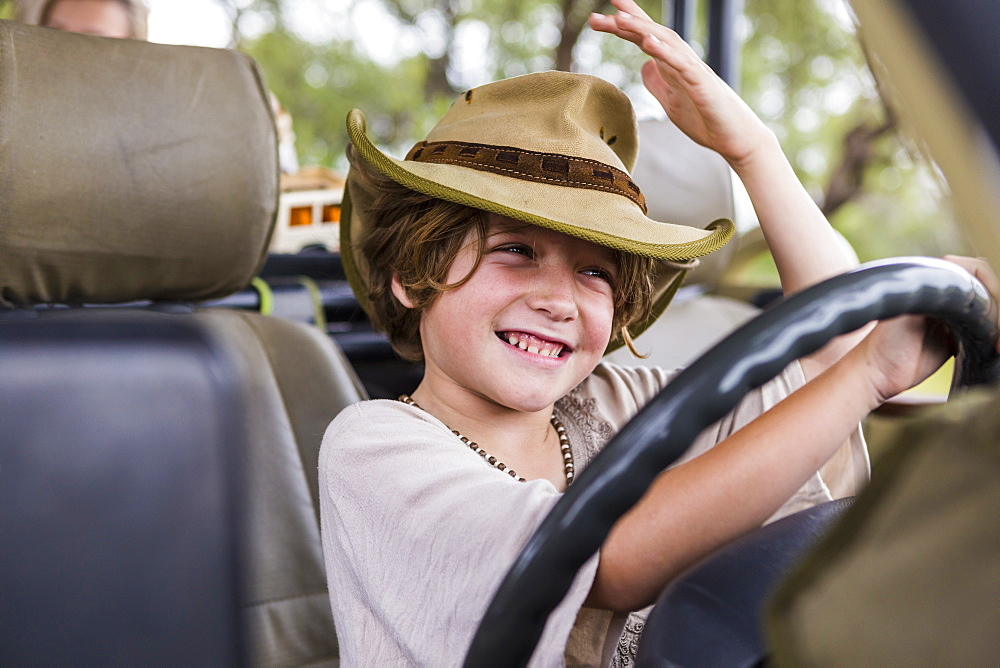 Smiling Six year old boy in the driving seat of a safari vehicle