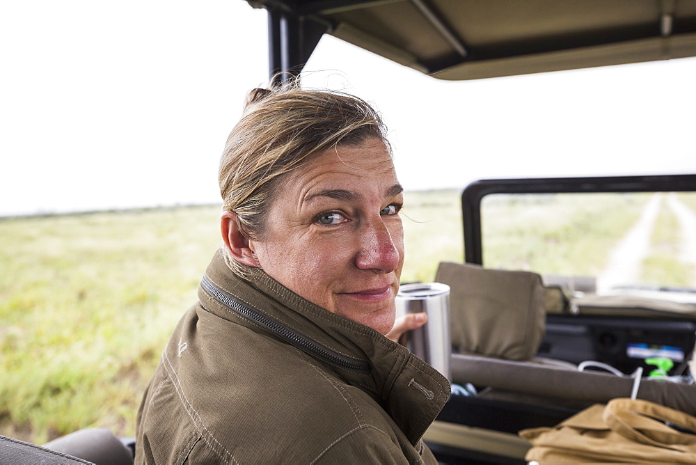 Portrait of adult woman in the front seat of a safari vehicle looking over her shoulder