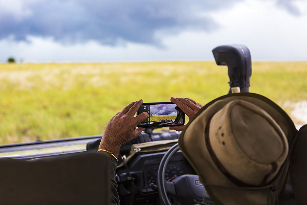 A safari guide taking smart phone picture of approaching storm clouds