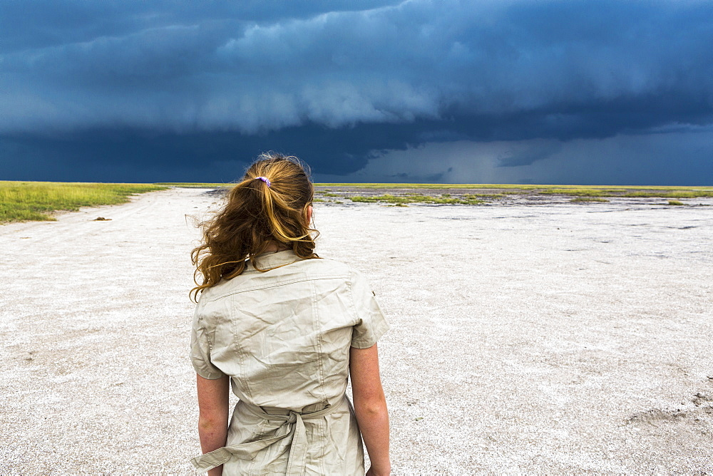 rear view of Thirteen year old girl looking at dramatic sky, Nxai Pan, Botswana