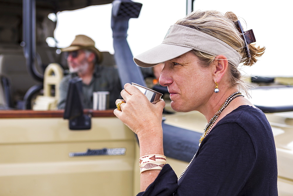 adult woman sipping coffee on safari, Nxai Pan, Botswana