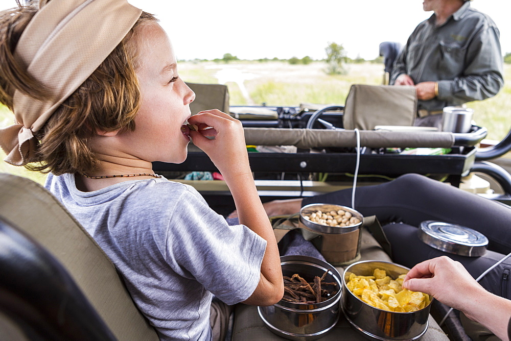 Six year old boy eating snacks in safari vehicle, Botswana