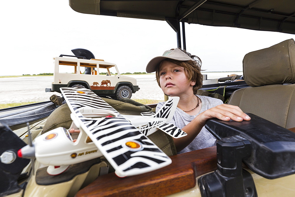 Six year old boy with toys in safari vehicle, Botswana