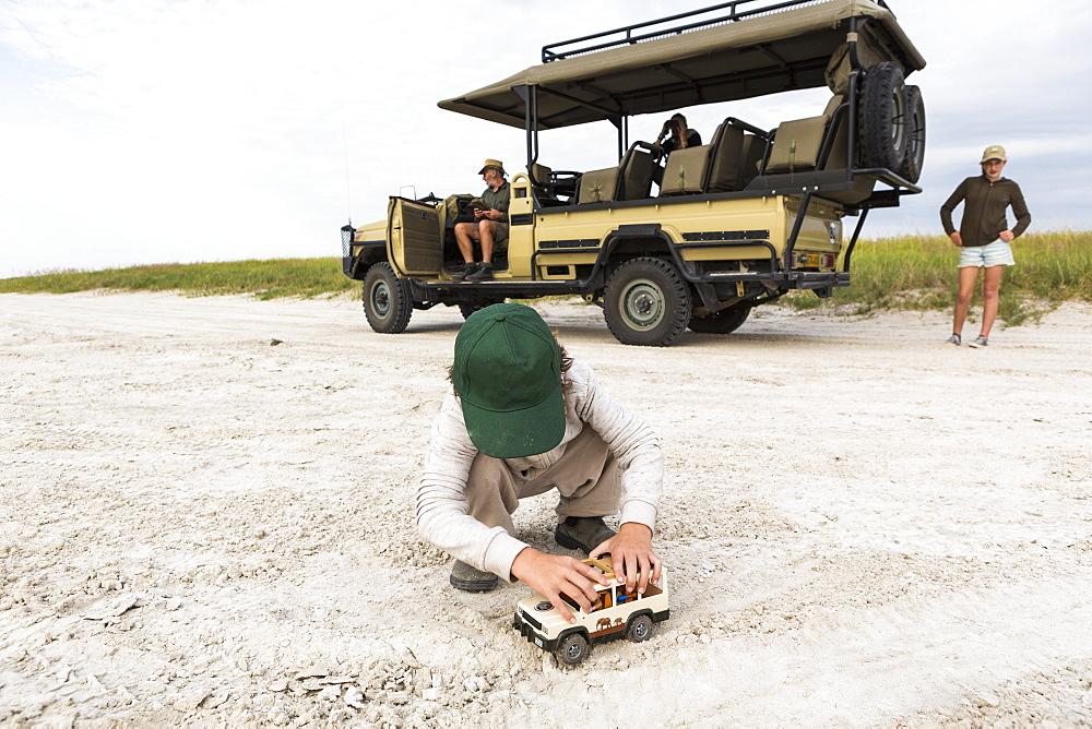 Six year old boy playing with toys, Nxai Pan, Botswana