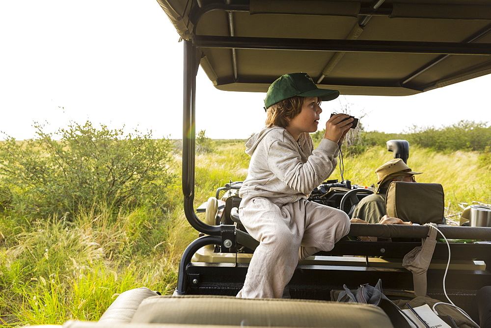 Six year old boy with binoculars in safari vehicle, Botswana