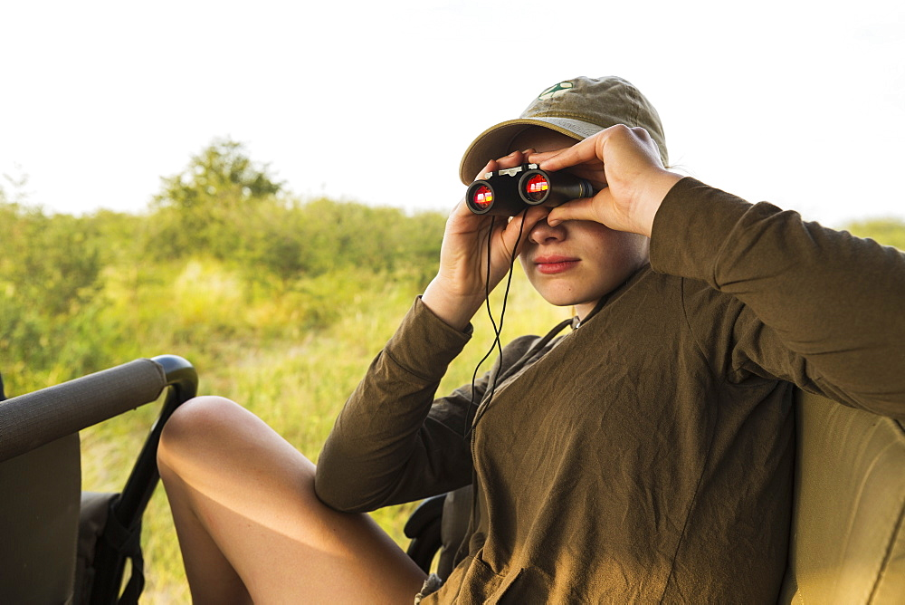 Thirteen year old girl with binoculars on safari vehicle, Botswana