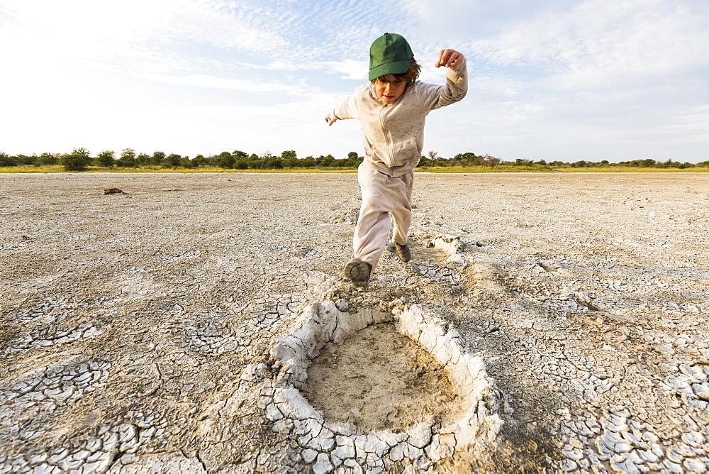 Six year old boy leaping into elephant footprints, Nxai Pan, Botswana