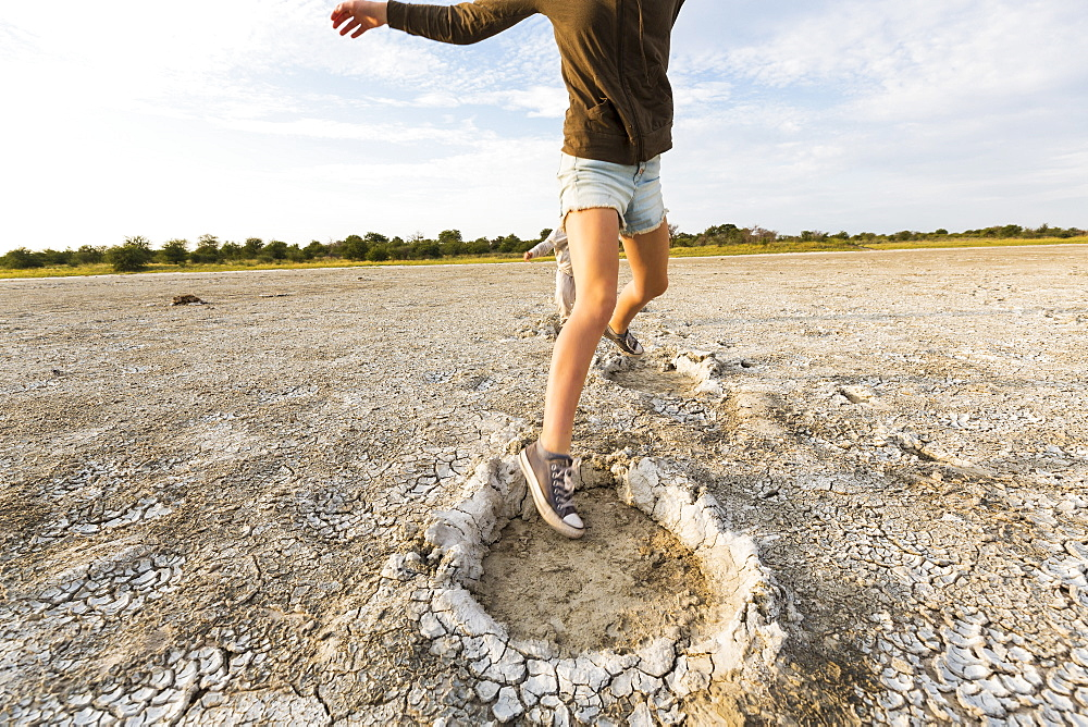 Thirteen year old girl leaping into elephant footprints, Nxai Pan, Botswana