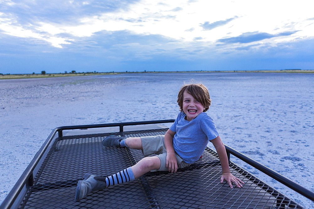 Six year old boy and guide on top of safari vehicle, Nxai Pan, Botswana
