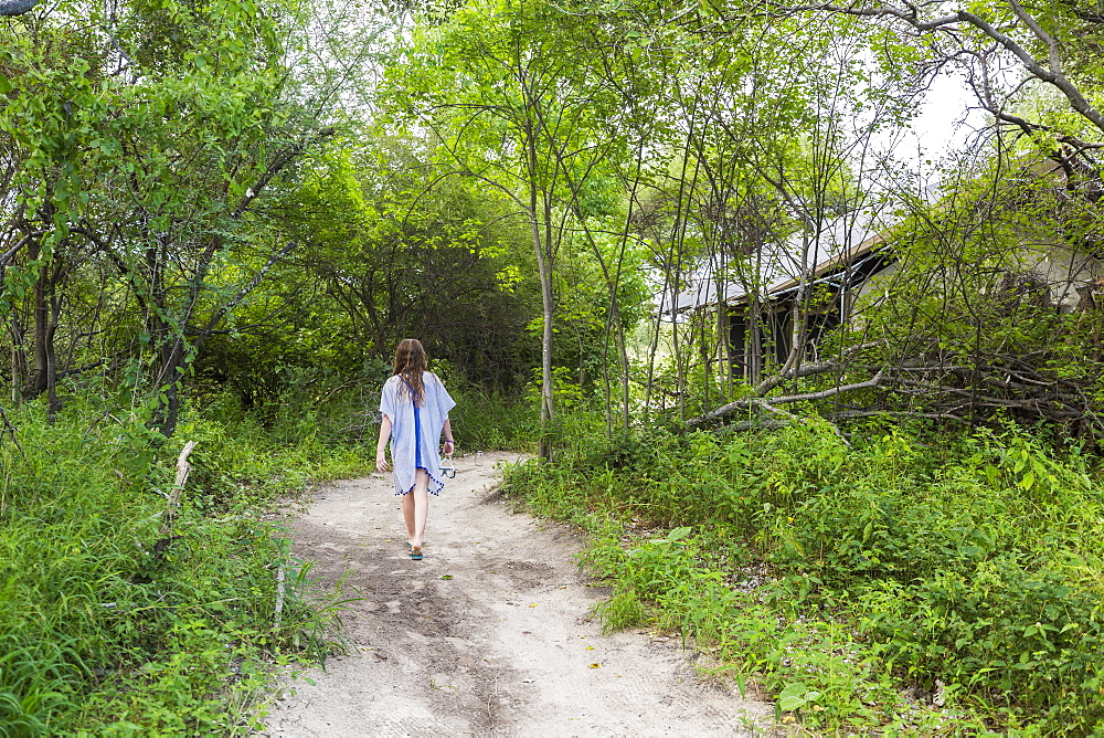 Thirteen year old girl walking on dirt path to tented camp, Maun, Botswana