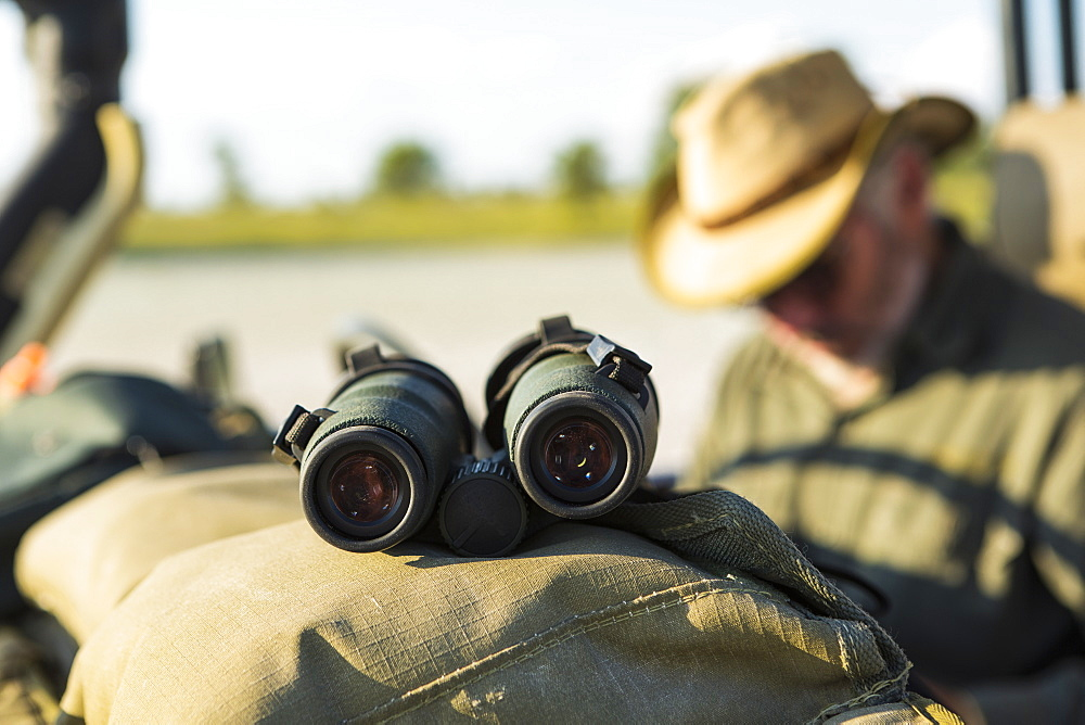 Binoculars on the dash of a safari jeep, a safari guide in the background