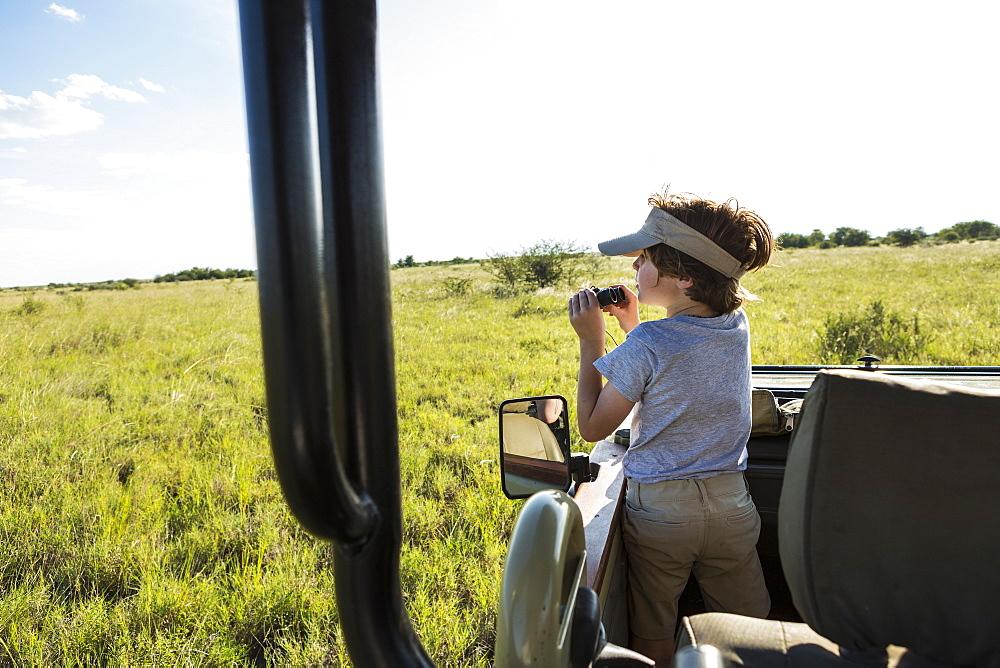 A six year old boy with binoculars in a safari vehicle
