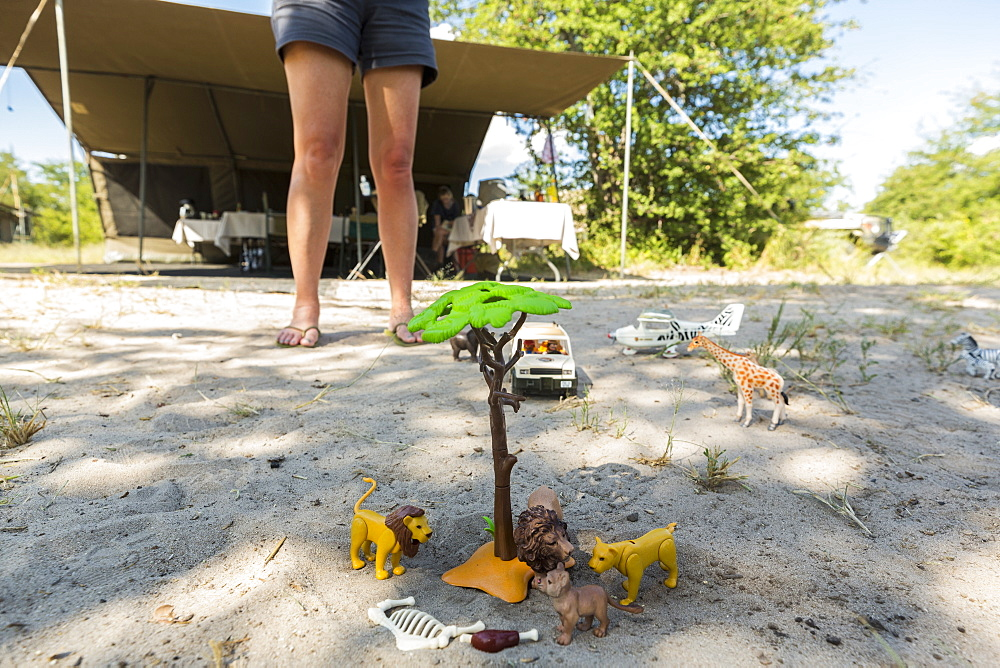 A safari scene on the sand, toy jeeps and safari animals on the ground, and an onlooker's legs