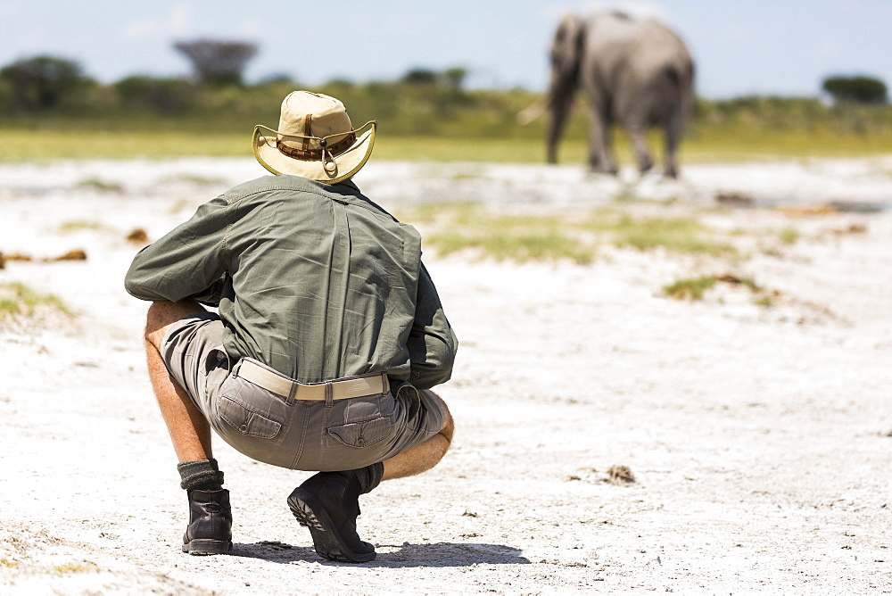 A guide crouching close to an elephant in Nxai Pan, Botswana