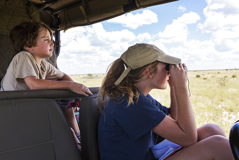 brother and sister in safari vehicle