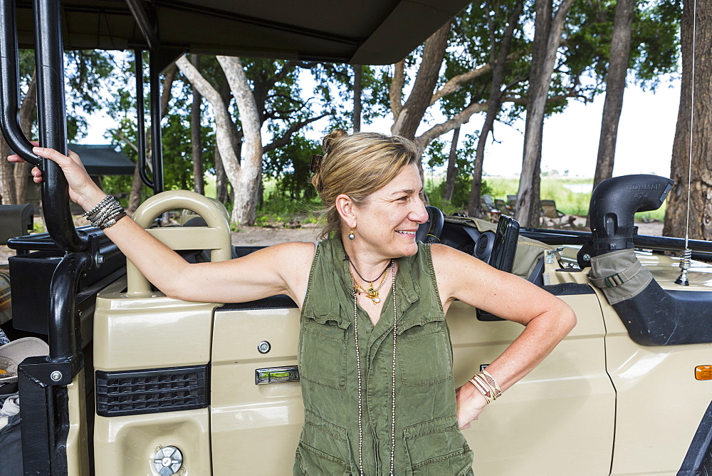 portrait of adult woman leaning on safari vehicle, tented camp, Botswana