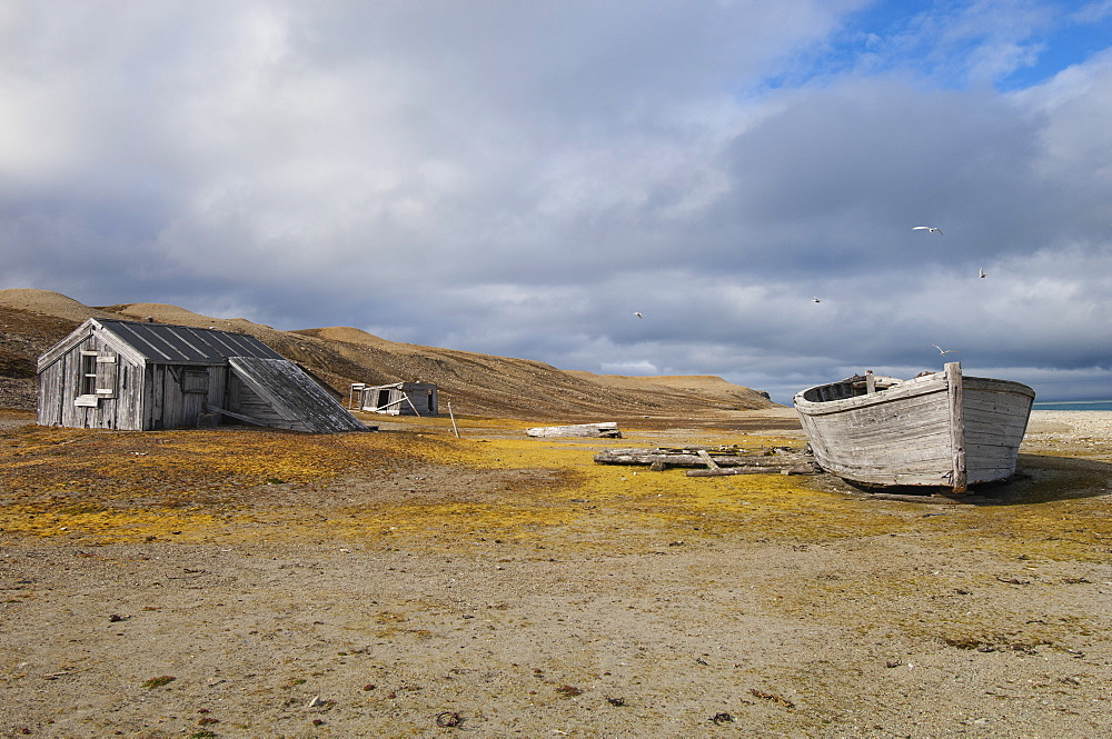 A small log cabin, a fishing hut with a beached boat, Svalbard, Norway