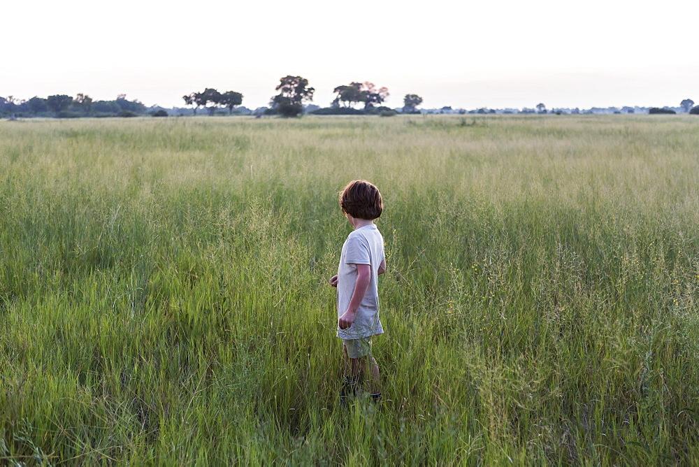 Six year old boy in field of grass, Botswana