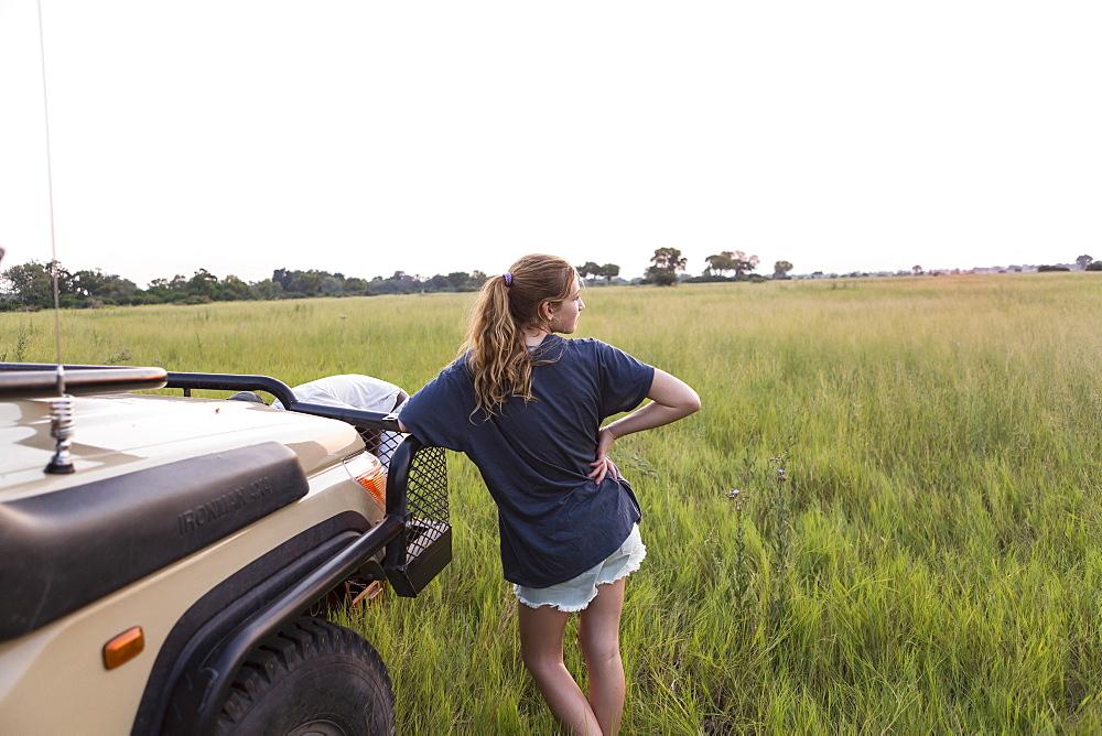 Thirteen year old girl leaning on safari vehicle, Botswana