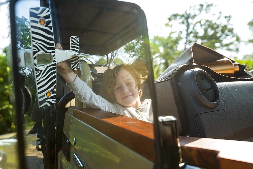 portrait of smiling Six year old boy in safari vehicle, Botswana