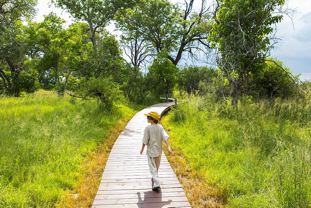 Six year old boy walking on wooden walkway in a safari camp