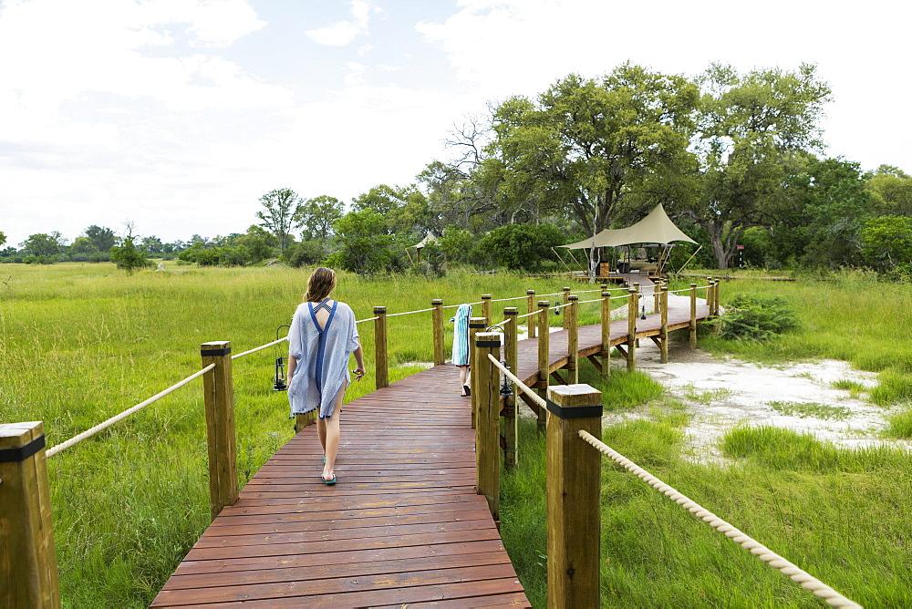 Thirteen year old girl walking on wooden path, tented camp, Botswana
