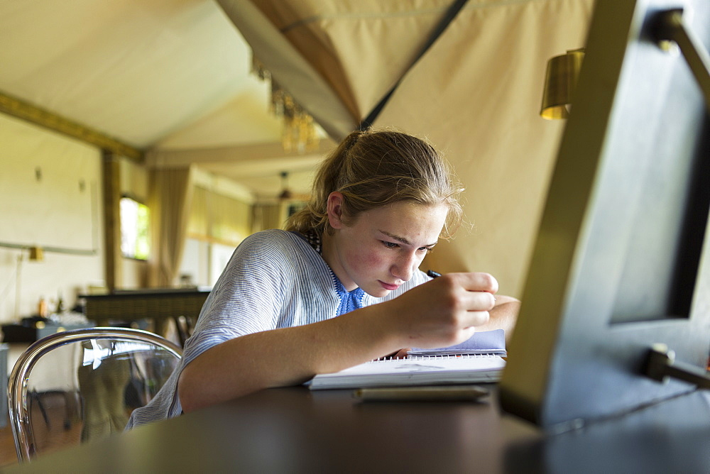 Thirteen year old girl writing in her journal, tented camp, Botswana