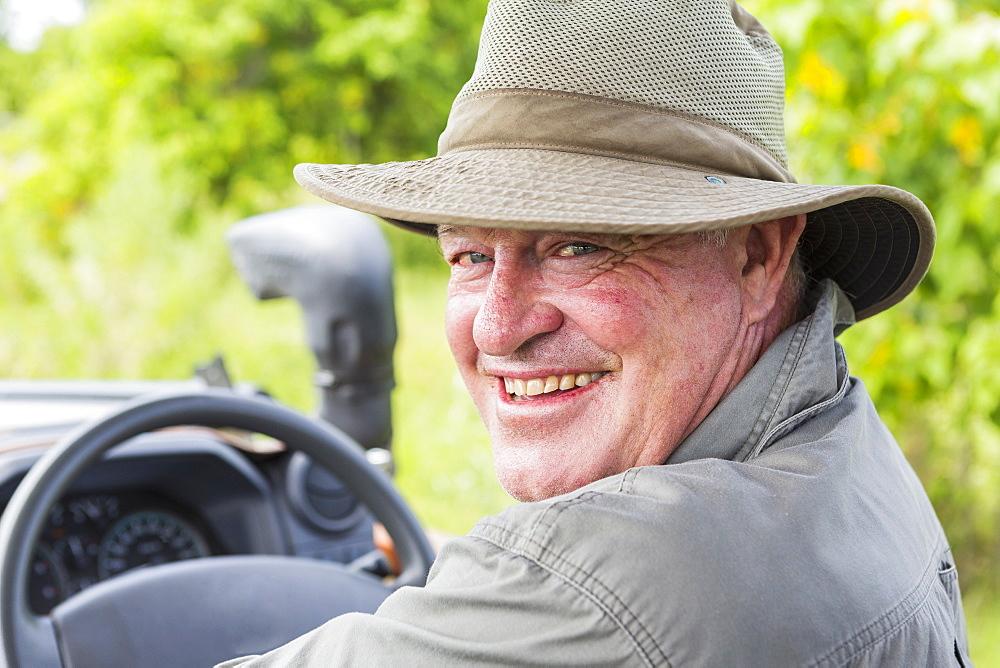 Portrait of smiling safari guide in a bush hat