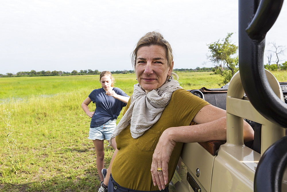 portrait of adult woman leaning on safari vehicle, Botswana