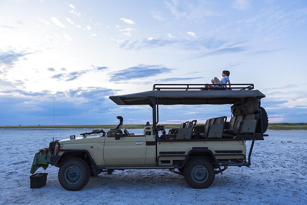 A six year old boy and his teenage sister sitting on top of a safari vehicle at dusk, Makgadikgadi Pan National Park, Botswana