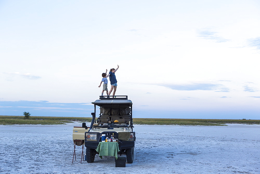 A brother and sister standing on top of a safari vehicle at dusk in a salt pan landscape, Makgadikgadi Pan National Park, Botswana