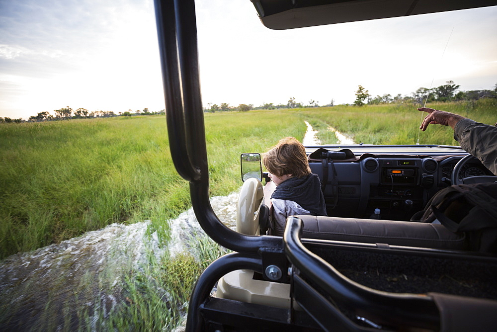 A six year old boy riding in safari vehicle looking out over the landscape, Botswana