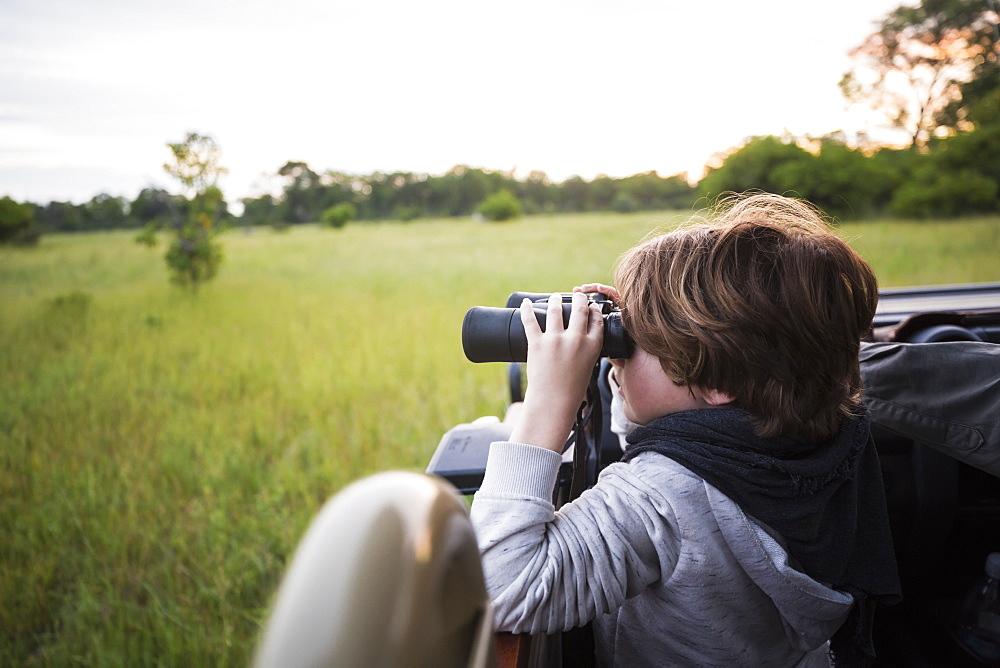 A six year old boy using binoculars seated in a safari jeep, Botswana
