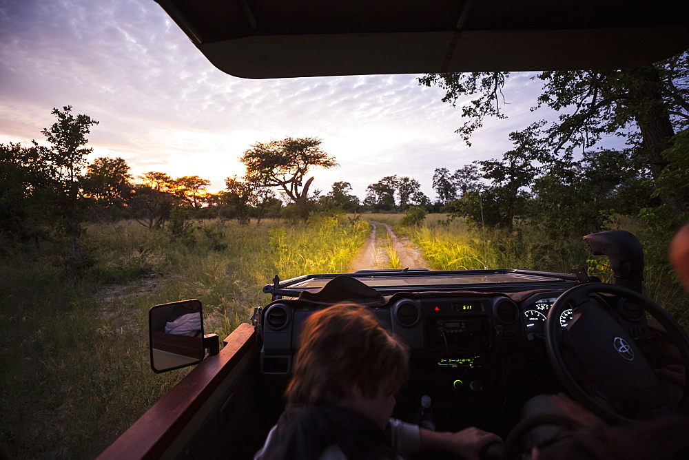 Motion blur, a safari vehicle driving on a dirt track with headlights on after sunset, Botswana