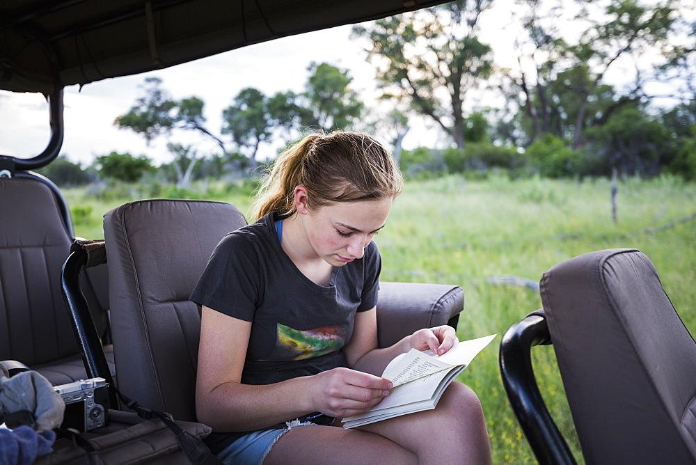 Thirteen year old girl writing in her journal seated in a jeep on safari, Botswana