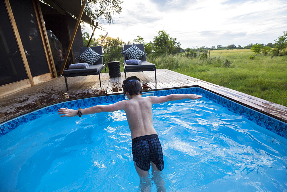 A six year old boy diving into a swimming pool at a tented camp, Botswana
