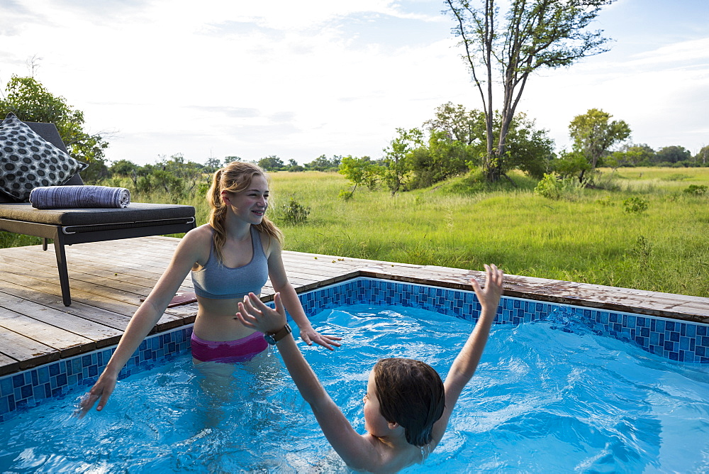 Brother and sister, Two children swimming in small pool at a safari camp, Botswana